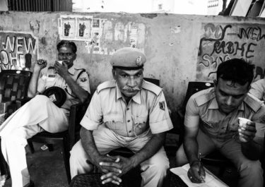 Black and White Photography with the title 'India 6'. Portrait of Indian Police Men sitting in front of a wall