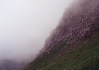 Analogue landscape photography of mountaintops surrounded by clouds with the title 'Massif I' - friendmade.fm