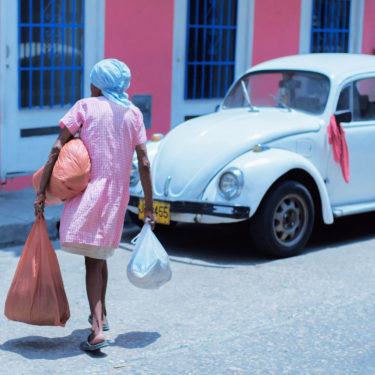 A street photography artwork with the title 'Cartagena'. Showcasing a woman crossing the street with bags in her hands. Scene from Colombia.