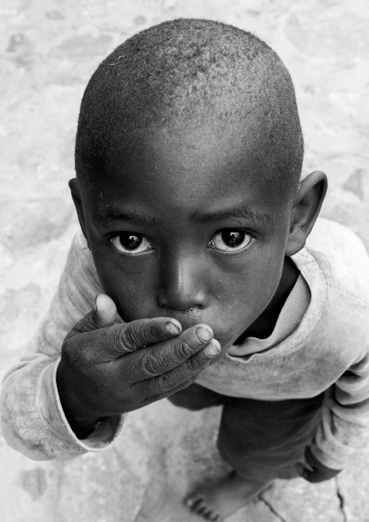 Black and white photogrpahy with the title 'Africa V'. A portrait of a little boy looking up to the camera. From the series 'Children of Tanzania'.