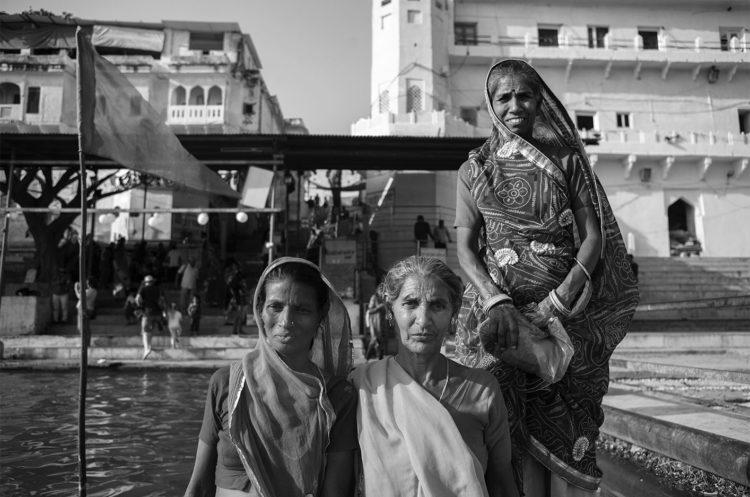 Schwarz-Weiss Fotografie mit dem Titel 'India 25'. Porträt von drei traditionell gekleideten Frauen, die auf einem Boot stehen.