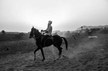 india 21 - black and white portrait of an Indian man riding a horse - photographed by Will Falize - friendmade.fm
