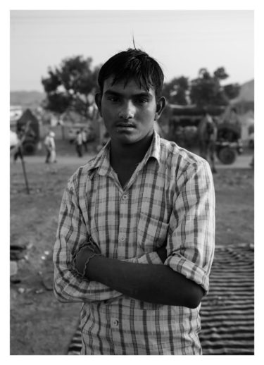india 19 - black and white portrait of a young indian man facing the camera and standing with his arms crossed - by Will Falize - friendmade.fm