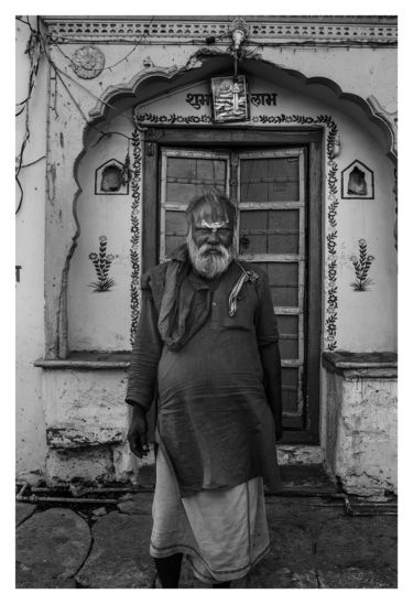 India 17 - black and white portrait of an indian man standing in front of a house - by Will Falize - friendmade.fm