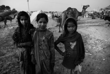 india 26 - black and white portrait of three indian girls in front of a camel - photographed by Will Falize - friendmade.fm